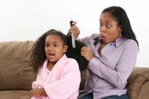 Mother combing her daughter's hair with a hair brush
