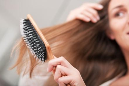 Junge Frau bürstet sich die Haare